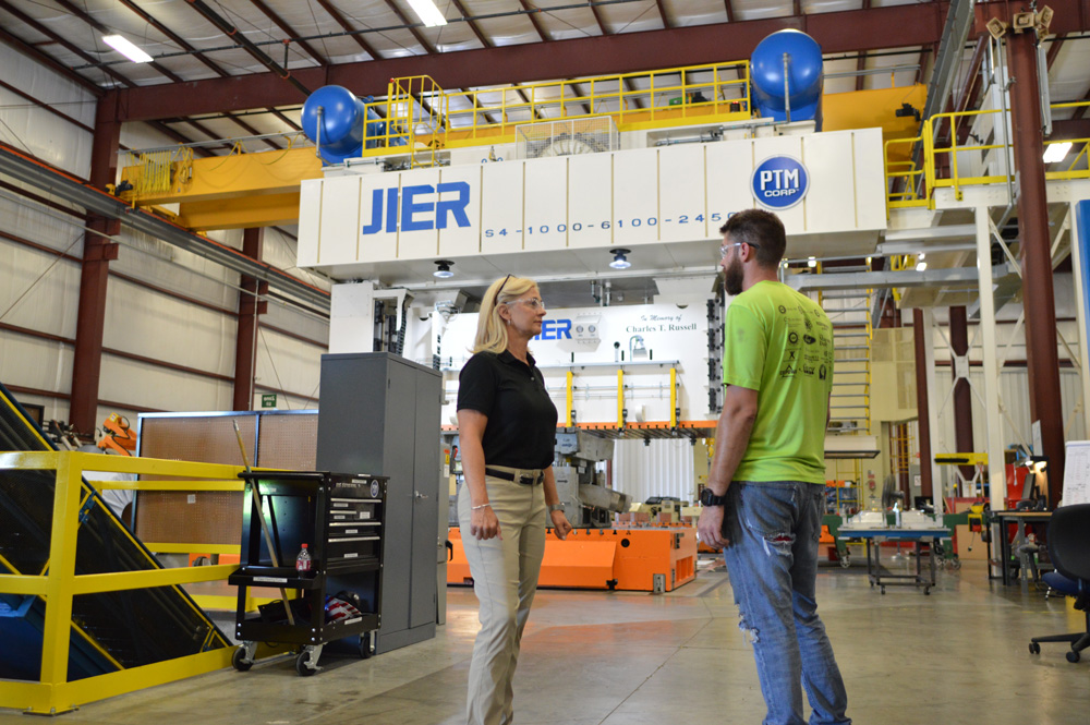 man and woman in front of industrial equipment