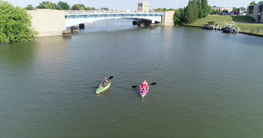 kayakers on river with bridge in background