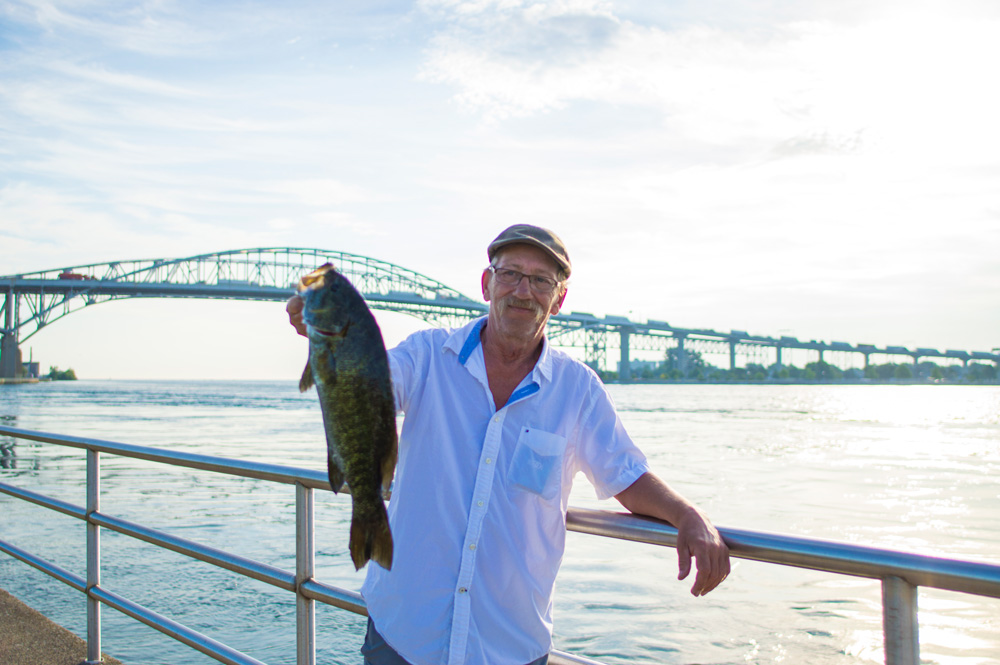 man holding fish with bridge in background